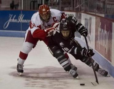 Derek Army (right), giving the slip last month to Boston University's Garrett Noonan, has played a big part in the Friars' hockey resurgence under coach Nate Leaman.